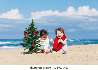Happy children with Christmas tree on the beach
