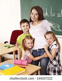 Happy children in classroom near blackboard.