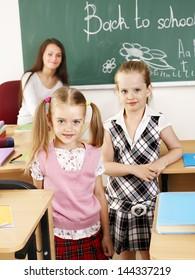 Happy children in classroom with teacher.