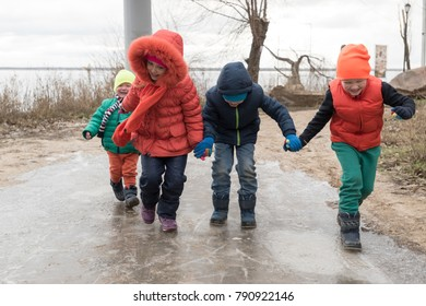 happy children in colorful clothes came on an excursion to the shore of the reservoir. Emotional children enjoy the sunny day and glide on the ice of a frozen puddle.