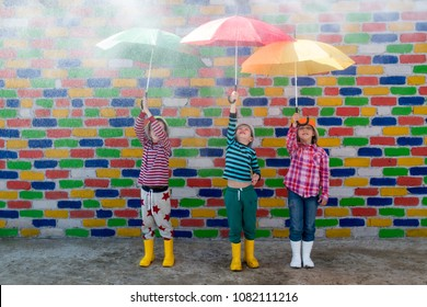 Happy children in colorful hats are sheltered from the rain under multicolored umbrellas in front of mottled brick wall. Fun during summer holidays. Boys and girl have funny time. Copy space