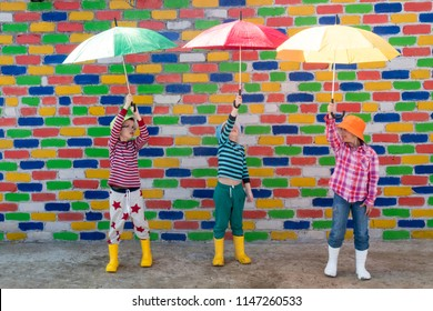 Happy children in colorful hats are sheltered from the rain under multicolored umbrellas in front of mottled brick wall. Fun during the summer holidays. Boys and girl have funny time