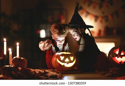 happy children in costumes of witch and vampire  in a dark house in   holiday Halloween