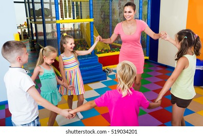 happy children dancing with teacher to music in class at school
