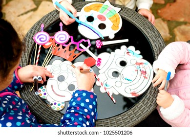 Happy children draw with pencils clown mask. Close up of hands little boy and girls sitting in playroom at the table near Party accessory's and painting. Purim, fools day, Halloween, birthday concept.