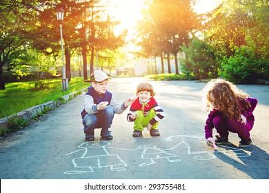 Happy children is drawing on asphalt in spring park. Background toning for instagram filter.
