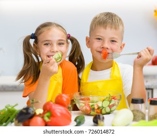 Happy children eat vegetables in the kitchen