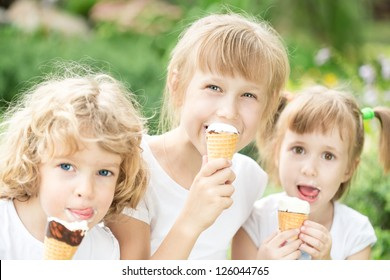 Happy children eating ice-cream outdoors in park