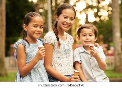 Happy children eating ice-creams and looking at the camera