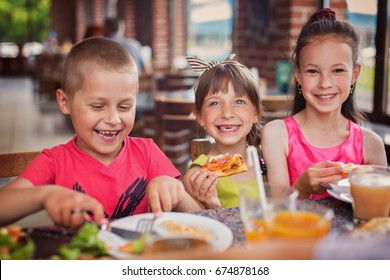Happy children eating pizza and having fun together