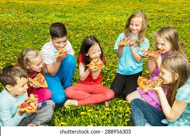 Happy children eating pizza outdoors
