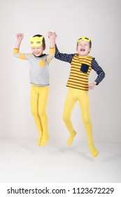 Happy children in elegant yellow clothes play at home. Boys in feline masks posing for a fashion magazine