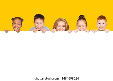 Happy children with empty board for your text isolated over yellow background, copy space - Shutterstock ID 1494899024