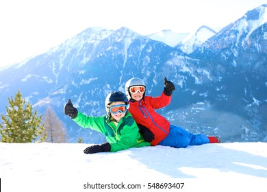 Happy children enjoying winter holidays in Alpine resort in Austria. Two brothers playing in the snow. Active sportive boys learning to ski. Beautiful Alps mountains in the background.