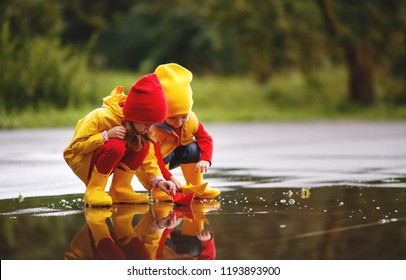 happy children girl and boy with paper boat in a puddle in autumn on nature