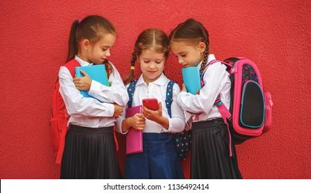 Happy children girls girlfriends schoolgirls student elementary school with a smartphone