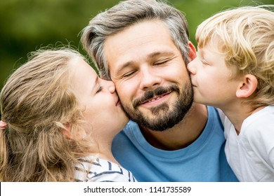 Happy children give father a kiss with love