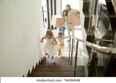Happy children going upstairs inside two story big house, excited kids having fun stepping walking up stairs running to their rooms while parents holding boxes, family moving in relocating new home