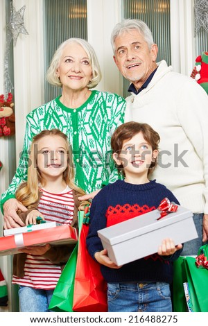 happy children with grandma and grandpa at christmas holding gifts - Grandpa For Christmas