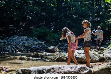 Happy children have fun by mountain creek at summer forest. Natural day light. Adventure.
