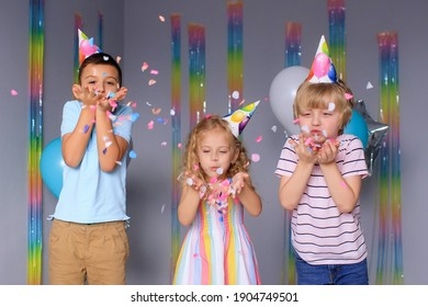 happy children have fun during the holidays and jump in colorful confetti