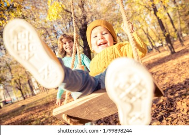 Happy children having fun outdoor in autumn park. Kids playing on swing against yellow blurred leaves background. Freedom and carefree concept - Shutterstock ID 1799898244