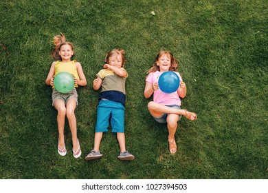 Happy children having fun outdoors. Kids playing in summer park. Little boy and two girls lying on green fresh grass, holding balloons