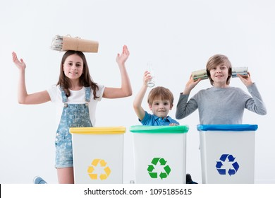 Happy children having fun while segregating household waste into bins with recycling symbol against white background