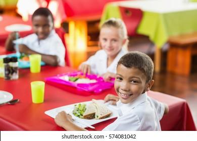 Happy children having lunch during break time in school cafeteria