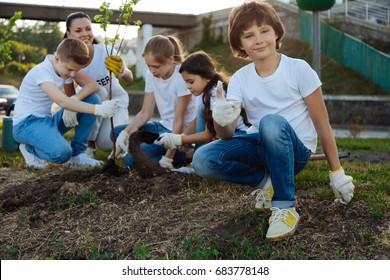 Happy children helping theirs teacher