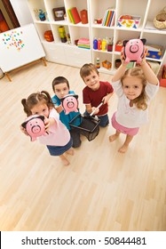 Happy children holding piggybanks
