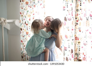 Happy children hug mom tightly, daughter and son gently hug and kiss mother, light interior near the window in scandinavian style, concept happy motherhood and emotions, mom with siblings