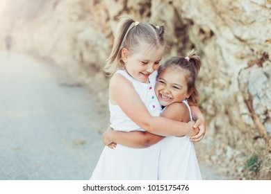 Happy children hugging each other. Kids having fun outdoors. Summer vacation and healthy lifestyle concept