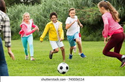 Happy children are jogning and playing football in the park.