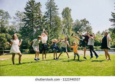 Happy children jumping or dancing in summer park