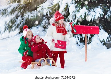 Happy children in knitted reindeer hat and scarf holding letter to Santa with Christmas presents wish list at red mail box in snow under Xmas tree in winter forest. Kids sending post to North Pole