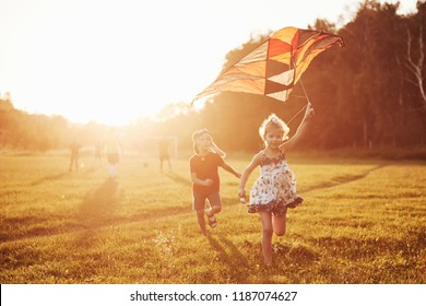 Happy children launch a kite in the field at sunset. Little boy and girl on summer vacation.
