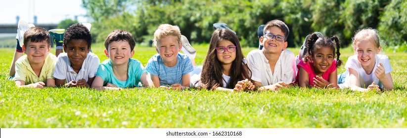 Happy children lie on the green grass on a sunny day