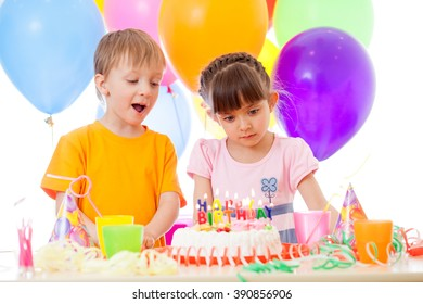 Happy children look at birthday cake