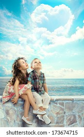 Happy children looking at blue sky with heart shaped clouds. People, happiness concept.
