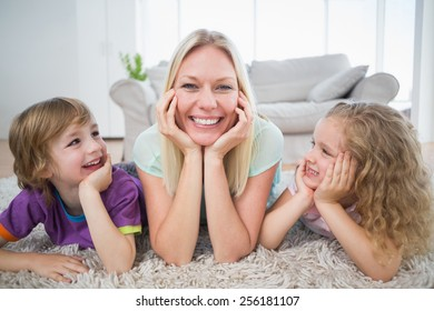 Happy children looking at mother lying on rug at home