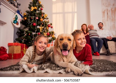 Happy children are lying on floor near Christmas tree and embracing dog. They are looking at camera and smiling. Parents are looking at them with proud
