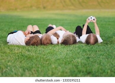 happy children lying on football pitch