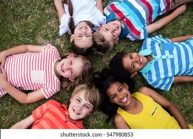 Happy children lying on grass in park