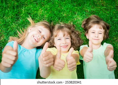 Happy children lying on green grass in spring park. Laughing kids showing thumbs up