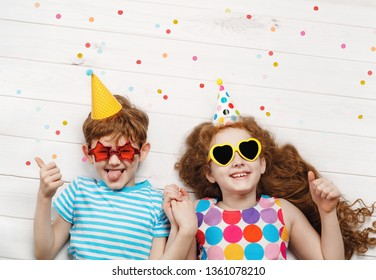 Happy children on carnival party, lying on a wooden floor. Happy childhood, Holiday concept.
