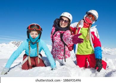 Des enfants heureux en vacances d'hiver en France jouent dans la neige fraîche et posent pour la caméra sur les pistes de ski
