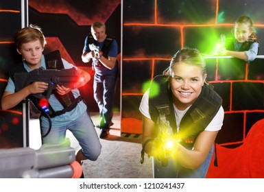 Happy children and parents aiming laser guns  during lasertag game in dark room