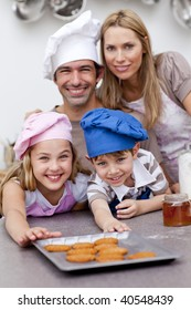 Happy children and parents eating cookies after baking in the kitchen