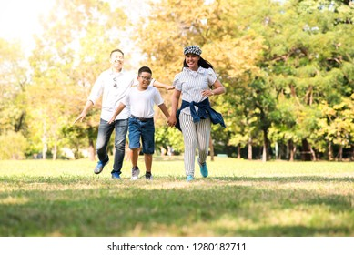 Happy children and parents playing in the park. Concept family relaxation.